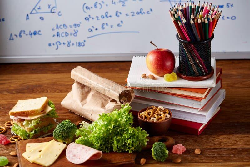 与健康午餐盒的学校午餐断裂和在木书桌,选择聚焦上的学校用品的概念 图库摄影