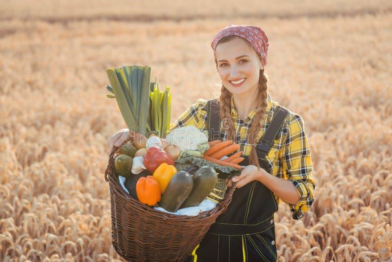 与健康和当地被生产的菜的妇女运载的篮子 免版税图库摄影