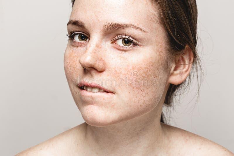 与健康皮肤叮咬嘴唇的年轻美丽的雀斑妇女面孔画象 库存照片