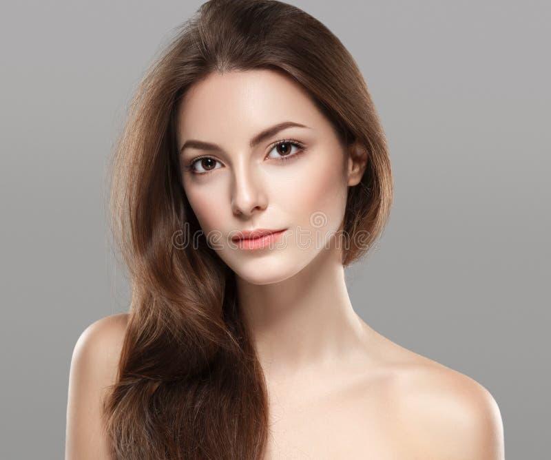 与健康皮肤的年轻美丽的妇女面孔画象在灰色背景 库存图片