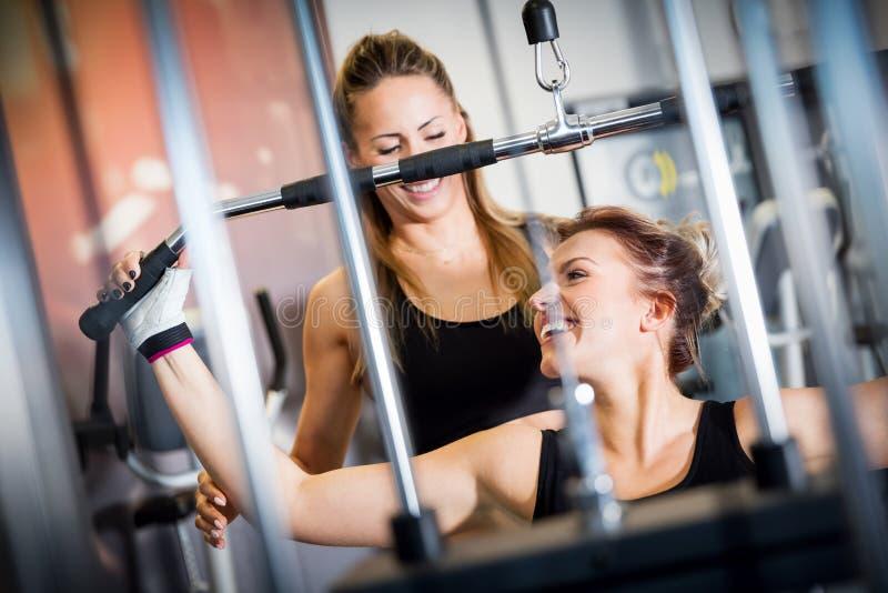 与健身房设备锻炼的个人教练员帮助 库存照片