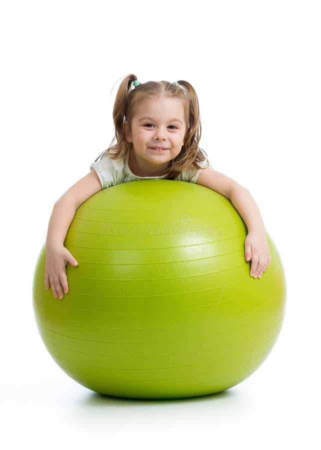 与健身球的微笑的俏丽的孩子 背景查出的白色 图库摄影