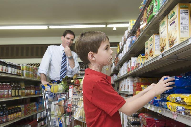 与儿子的父亲购物在超级市场 图库摄影