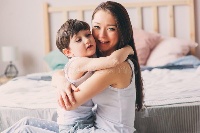 与儿童儿子的愉快的爱恋的母亲拥抱早晨在床上 库存图片