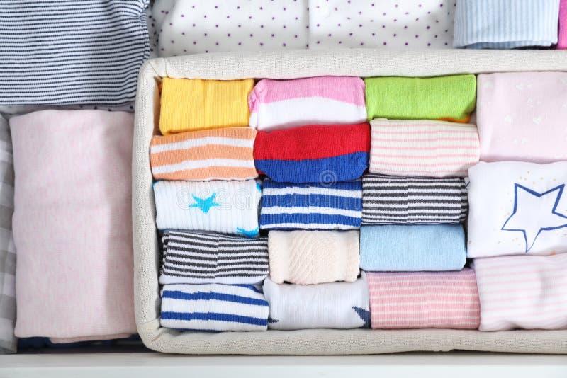 与儿童袜子的篮子在其他衣裳中 免版税库存照片