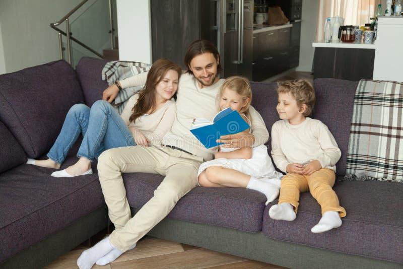 与儿童阅读书的愉快的家庭一起坐沙发 免版税库存图片