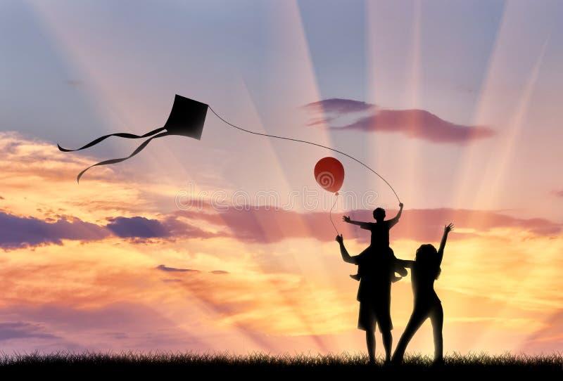 与儿童飞行风筝日落步行的年轻家庭 库存图片