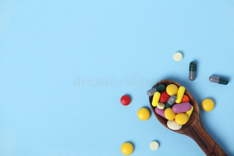与充分匙子的明亮的背景医疗药片 库存图片