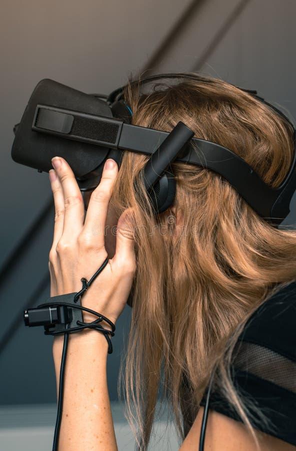 与充分的浸没的虚拟现实 女孩戴在她的头的虚拟现实眼镜 免版税图库摄影