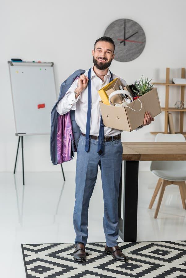 与充分纸板箱的商人办公用品和夹克在放弃工作的手上 库存图片