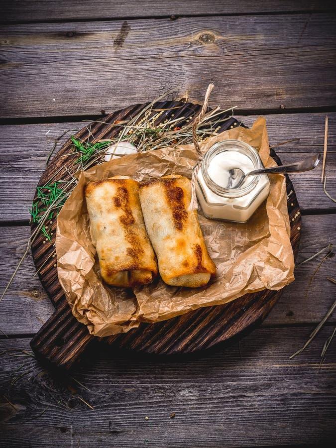 与充塞的薄煎饼和在一张木桌上的酸性稀奶油 库存图片