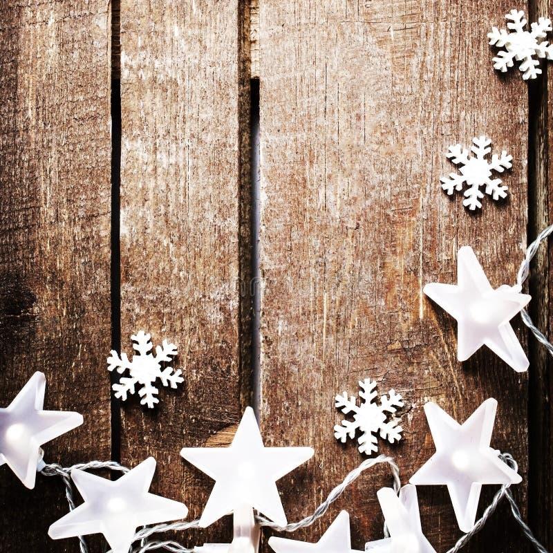 与光、雪花、星和f的圣诞节土气背景 免版税图库摄影