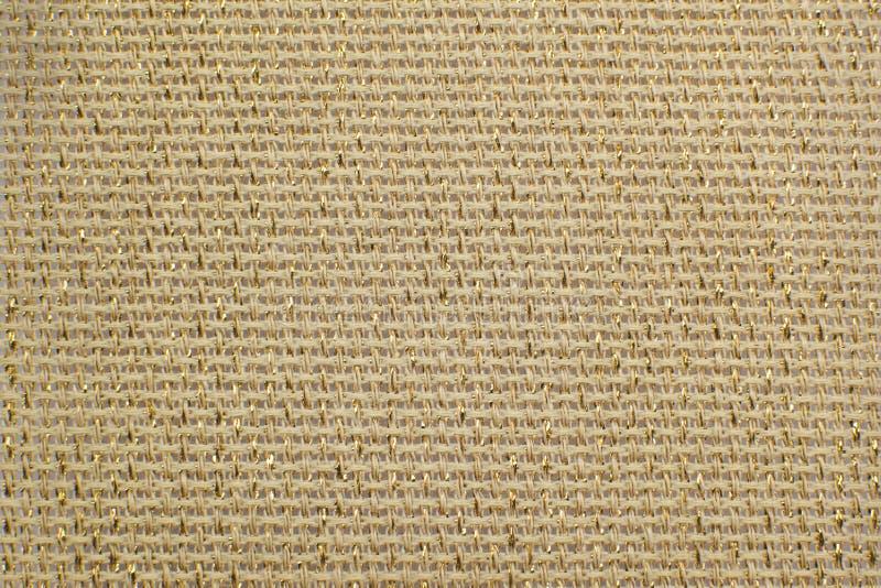 与光华金黄lurex特写镜头的米黄自然亚麻制织品 库存照片