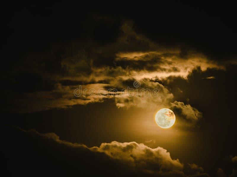 与光和秀丽多云天空的满月在黑暗的夜bac中 库存图片