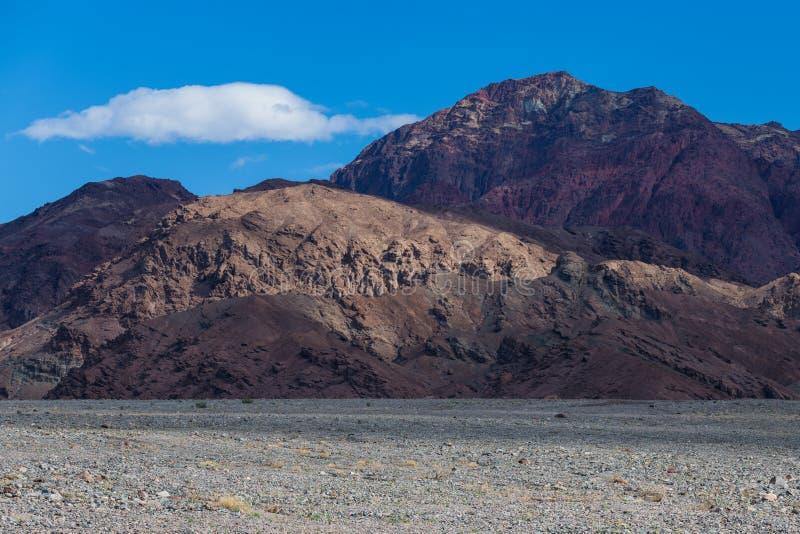 与光对比的区域的五颜六色,贫瘠沙漠在一天空蔚蓝下的山峰和阴影与白色松的云彩 免版税库存照片