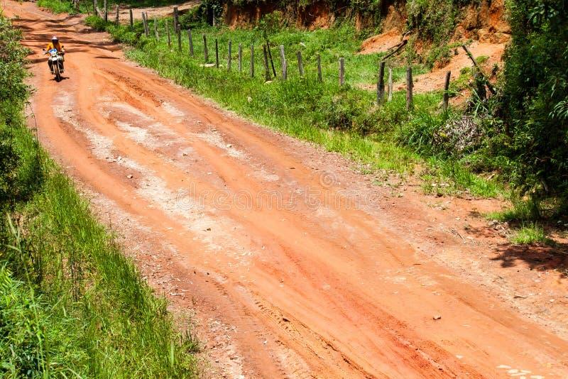 与光秃的地球红色参差不齐的不完美的表面的土路轨道与可看见的车轮胎轨道标记和摩托车骑士骑马 免版税库存图片