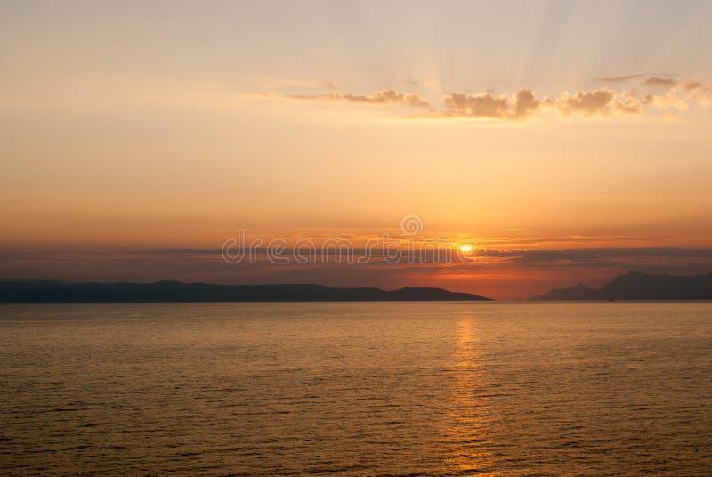 与光芒的金黄日落在云彩上,水平 免版税库存图片