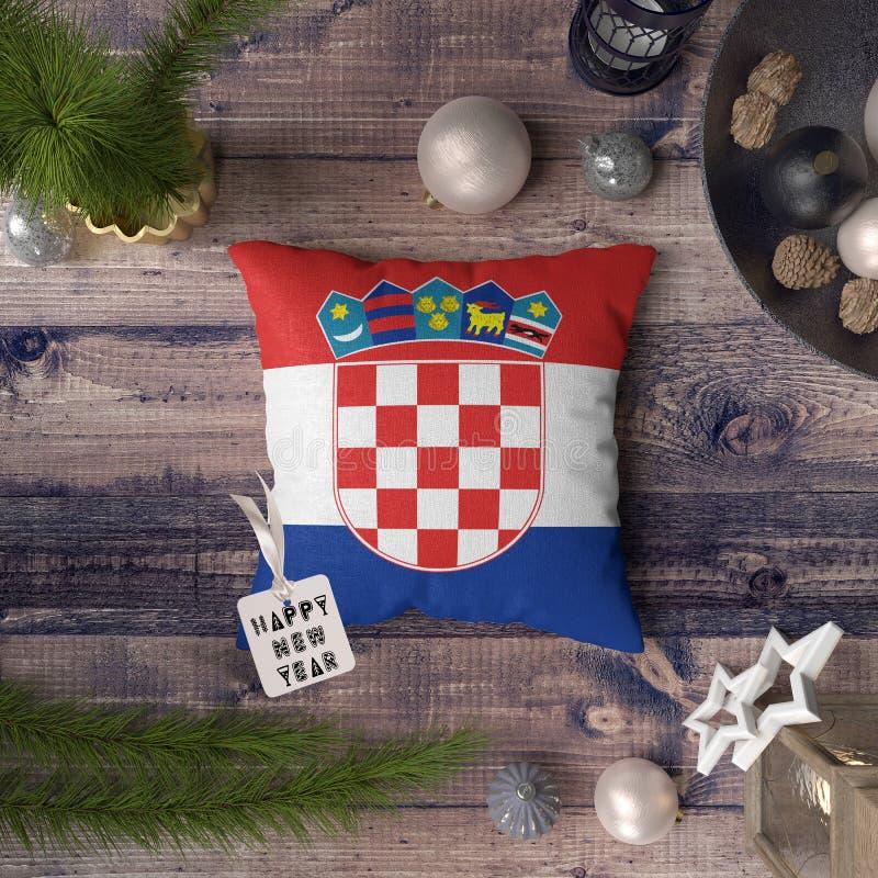 与克罗地亚旗子的新年快乐标记在枕头 在木桌上的圣诞装饰概念与可爱的对象 免版税库存图片