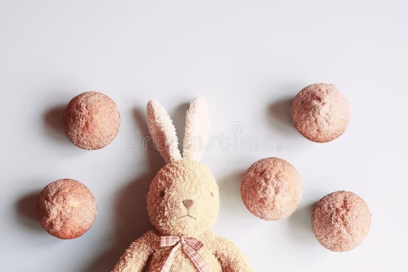 与兔宝宝和杯形蛋糕的愉快的复活节或生日贺卡 免版税图库摄影