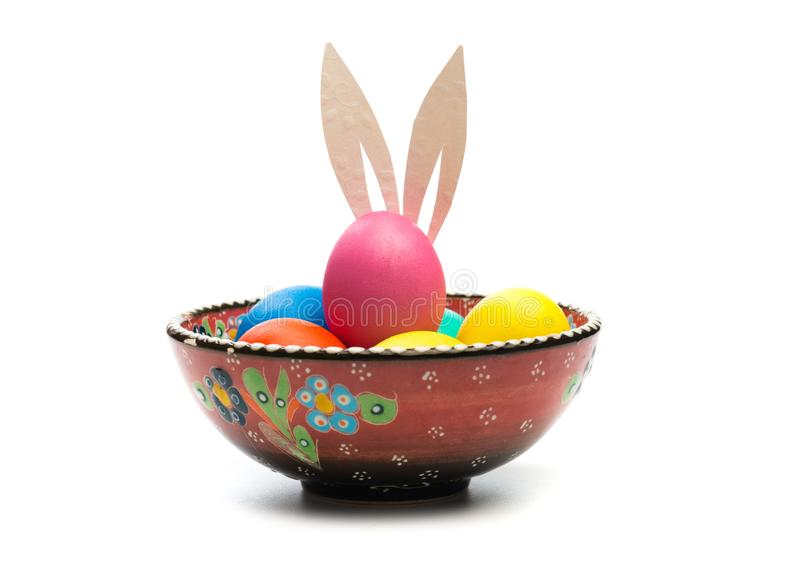 与兔宝宝耳朵的复活节彩蛋在被隔绝的碗 免版税库存图片