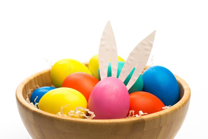 与兔宝宝耳朵的复活节彩蛋在被隔绝的碗 库存图片