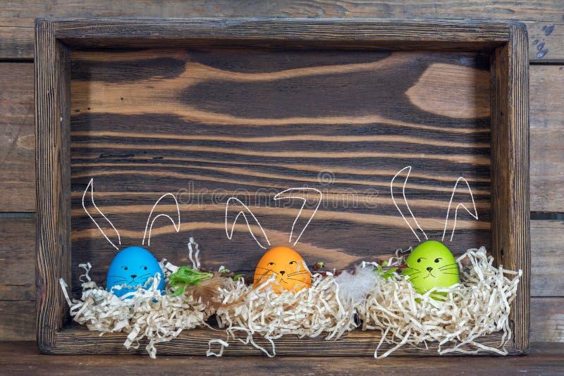 与兔宝宝耳朵的复活节彩蛋在箱子的巢 库存图片