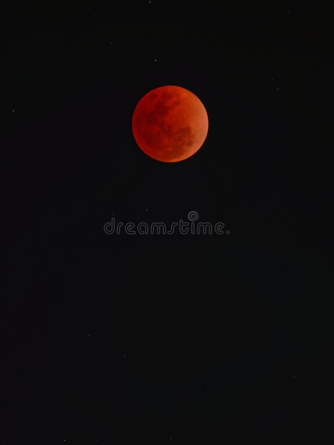 与全面月蚀的超级名门出身月亮在黑暗的天空背景 库存照片