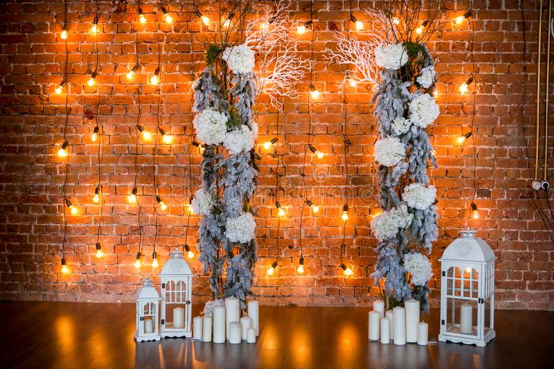 与八仙花属灌木、蜡烛和电灯泡的具球果分支在砖背景 免版税库存图片