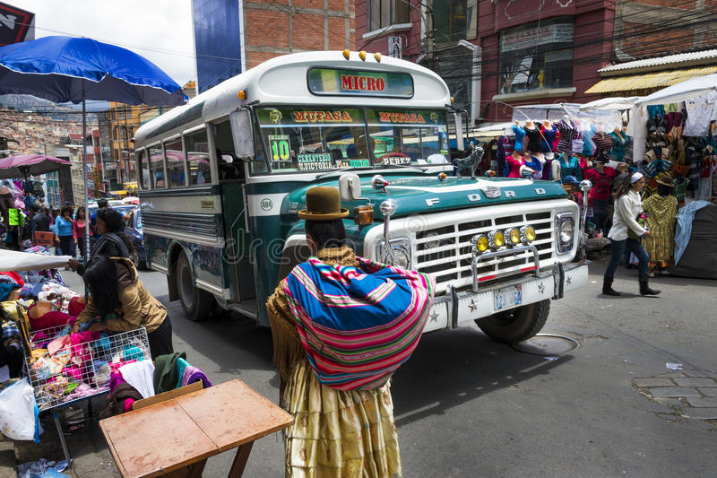 与公共汽车和人的拥挤的街场面在市拉巴斯,在玻利维亚 免版税库存照片