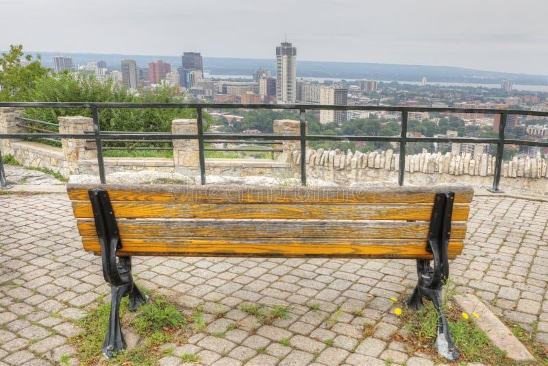 与公园长椅的哈密尔顿,加拿大地平线在前景 图库摄影