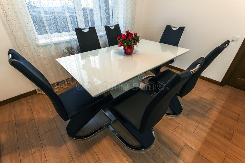 与六把椅子的白色木和玻璃圆的餐桌 现代设计、餐桌和椅子在当代厨房里 系列 免版税库存照片