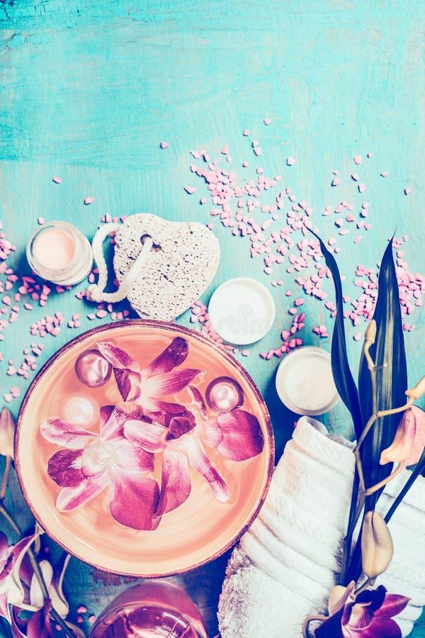 与兰花的健康设置开花漂浮在碗在绿松石破旧的别致的背景的水和温泉工具 图库摄影