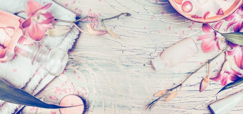 与兰花花和温泉工具的健康背景:奶油、化妆水、毛巾和水在破旧的别致的木背景,上面滚保龄球 免版税库存照片