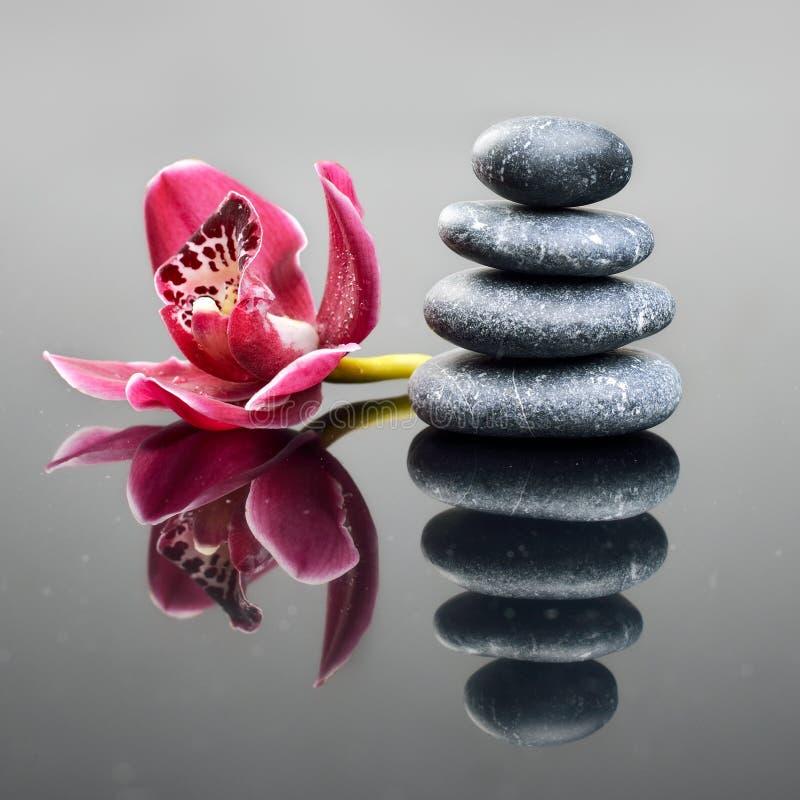 与兰花花和石头的温泉背景 免版税库存图片