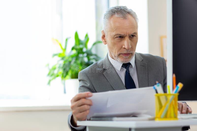 与关于屏幕的信息被混淆的有关的短发老办公室工作者 免版税库存图片