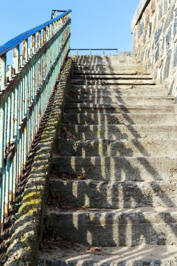 与具体垫脚石和金属扶手栏杆的被放弃的楼梯,照亮由太阳 免版税库存图片