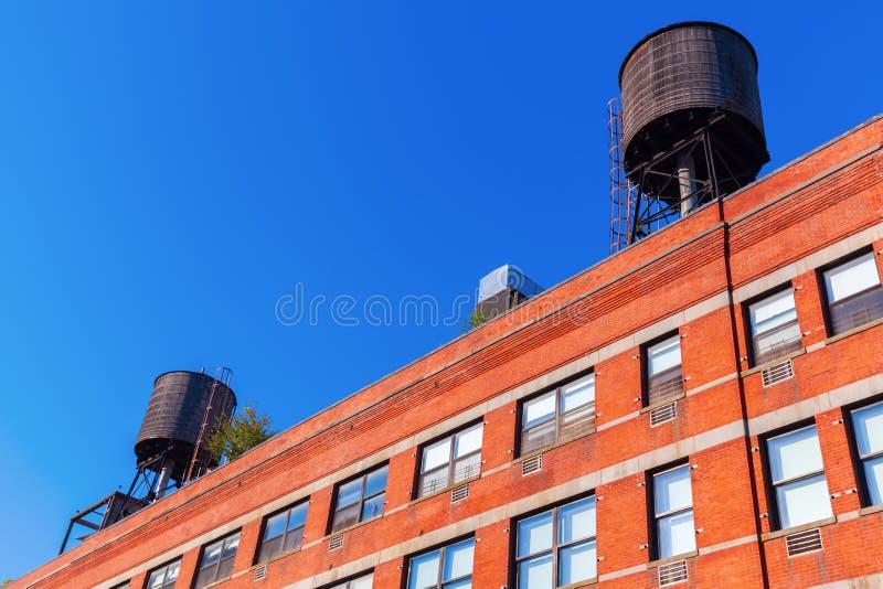 与典型的储水箱的砖瓦房在NYC的屋顶 免版税库存图片