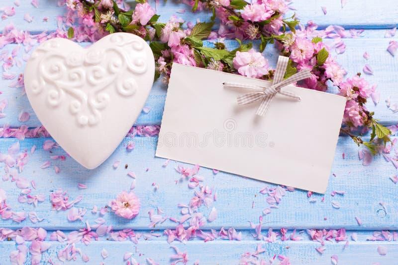 与典雅的佐仓的背景开花,白色装饰心脏 库存照片