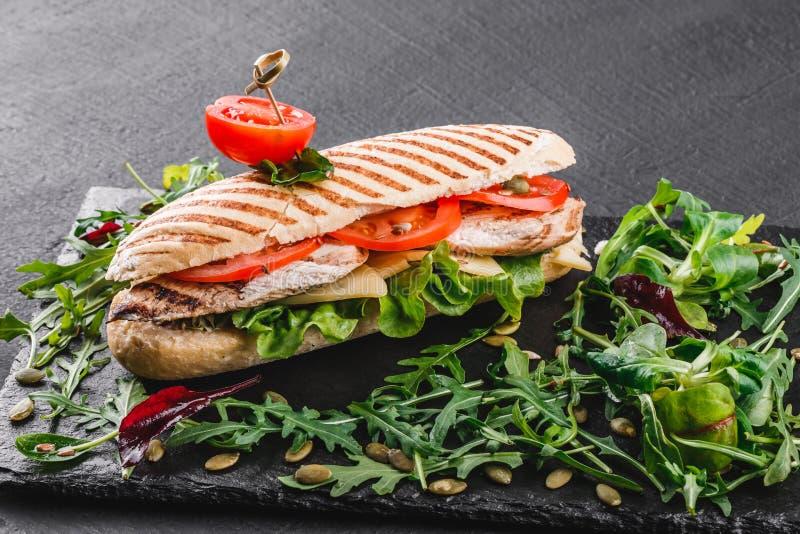 与内圆角烤鸡、新鲜蔬菜、乳酪和绿色的三明治在黑石背景的黑色页岩板 免版税图库摄影