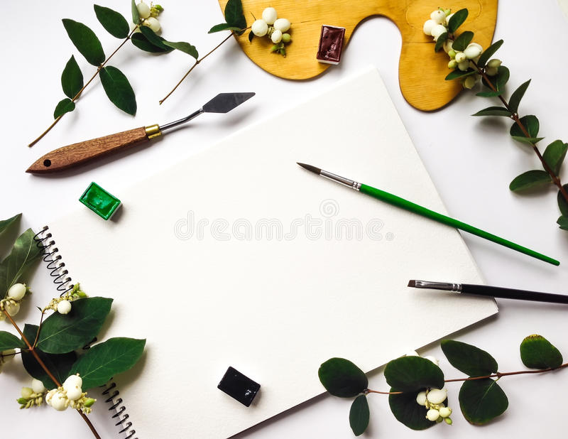 与册页、水彩和刷子的秋天构成,装饰用绿色雪果分支和莓果 平的位置,顶视图 库存照片
