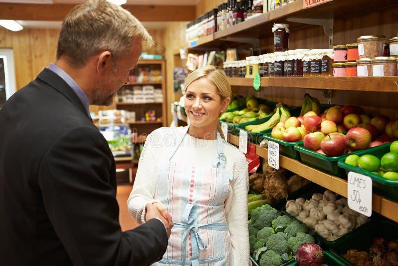 与农厂商店女性店主的银行经理会议  免版税库存照片