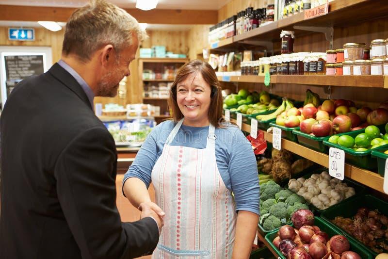 与农厂商店女性店主的银行经理会议  库存图片