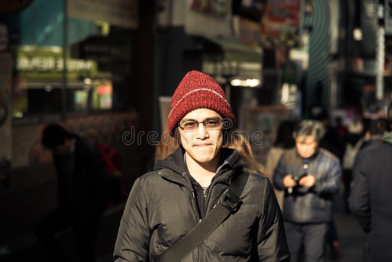 与冬天夹克的亚洲男性和帽子在城市instagram t站立 库存照片