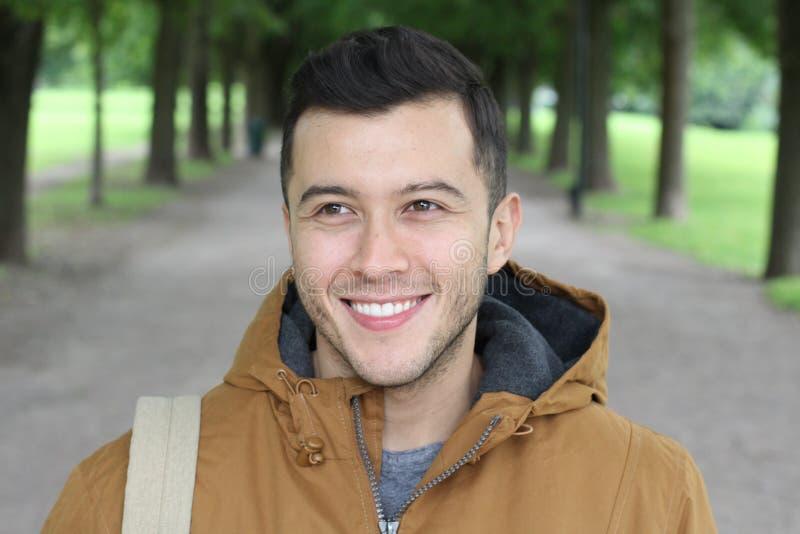 与冬天成套装备的时髦男性微笑在公园的 库存照片
