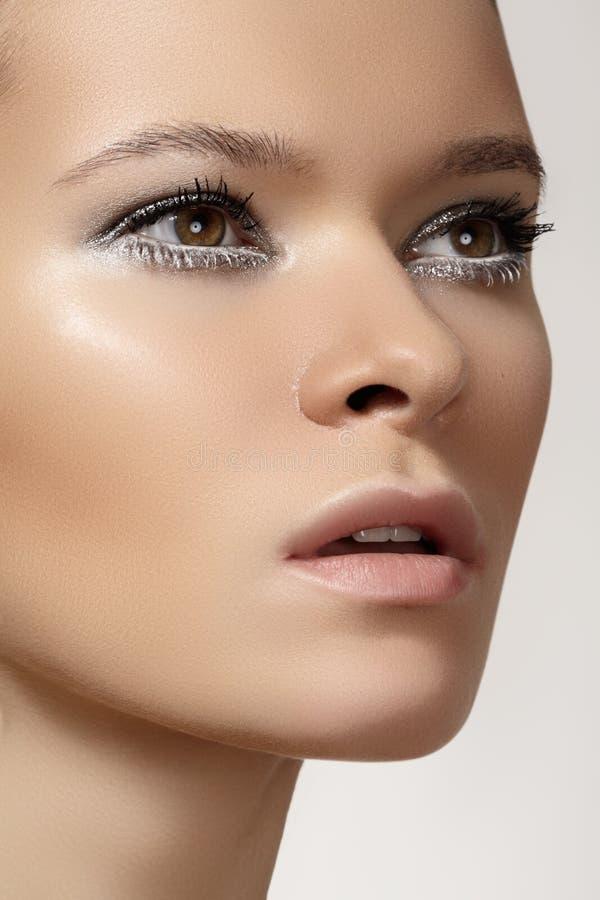 与冬天构成的美丽的时装模特儿表面,雪睫毛,发光的纯皮肤 免版税库存照片