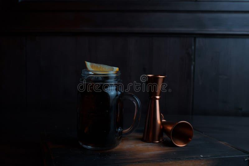 与冰、威士忌酒和可口可乐,柠檬切片的酒精鸡尾酒在一张木桌上站立在餐馆在金属旁边 免版税库存照片