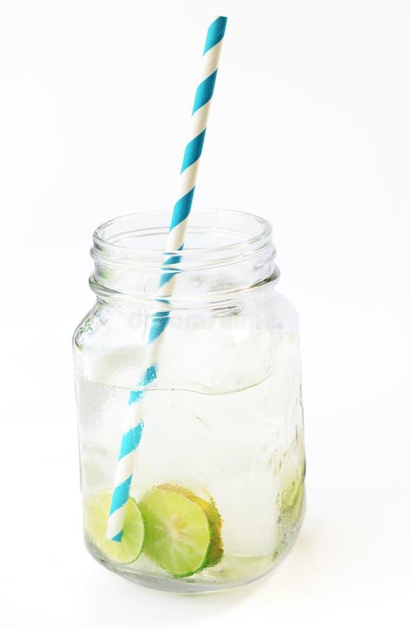 与冰、柠檬和石灰切片的柠檬水在有秸杆的一个瓶子 免版税库存照片