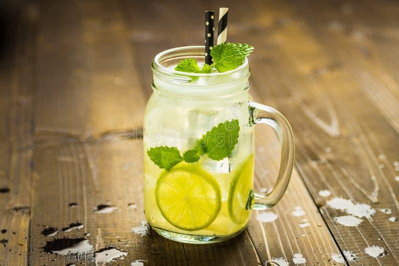 与冰、柠檬和薄荷叶的冷的新鲜的柠檬水Mojito鸡尾酒在金属螺盖玻璃瓶 免版税库存照片