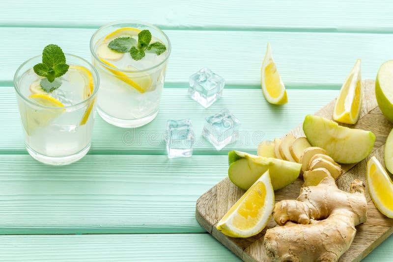 与冰、桔子和苹果切片的凉水在薄荷的绿色背景的夏天健康饮料的 免版税库存照片