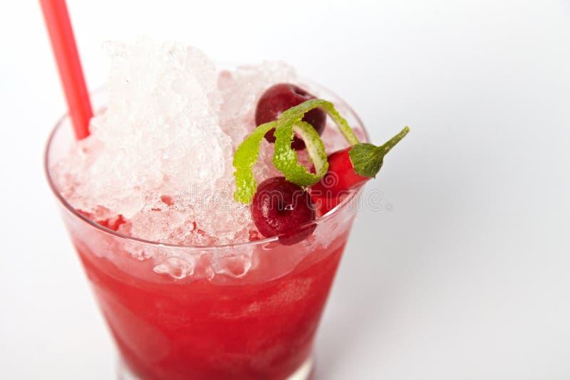 与冰、石灰、樱桃和辣椒的红色鸡尾酒饮料 免版税图库摄影